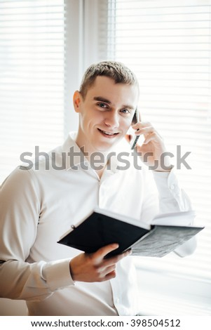 businesswoman with diary standing near window and talking on the phone - stock photo