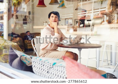 Businesswoman with digital tablet in a coffee shop - stock photo