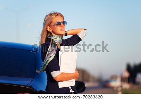 Businesswoman with financial reports against a highway - stock photo