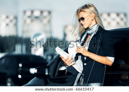 Businesswoman with financial reports against industrial background. - stock photo