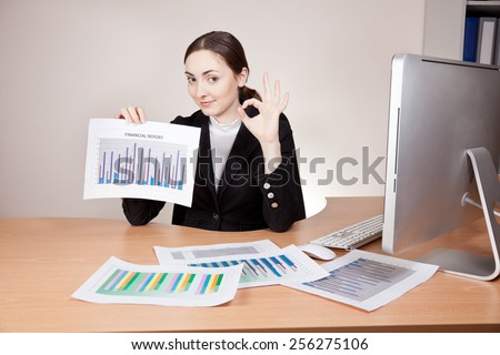 Businesswoman with financial reports at the office - stock photo