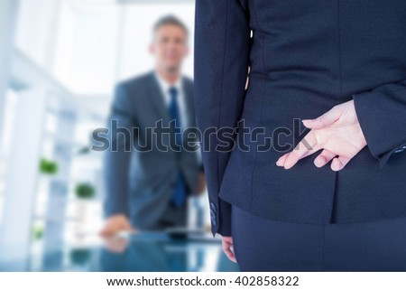 Businesswoman with fingers crossed behind her back against business people looking at camera behind desk - stock photo