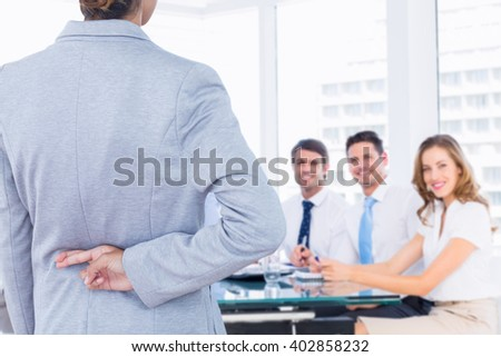 Businesswoman with fingers crossed behind her back over white background against business people in office at presentation - stock photo