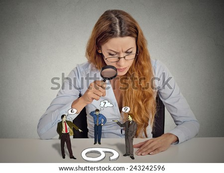 Businesswoman with glasses sitting at desk skeptically looking at arguing people through magnifying glass isolated grey office wall background. Human face expression, attitude. To each its own concept - stock photo