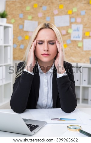 Businesswoman with hands to temples in front of computer. Office at background. Concept of headache. - stock photo