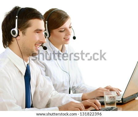 Businesswoman with headset smiling at camera in call center. Businessman in headsets on background