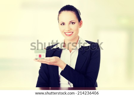Businesswoman with house model over white - real estate loan or insurance concept