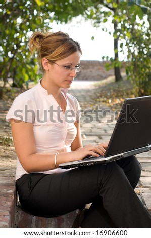 Businesswoman with laptop computer in the park