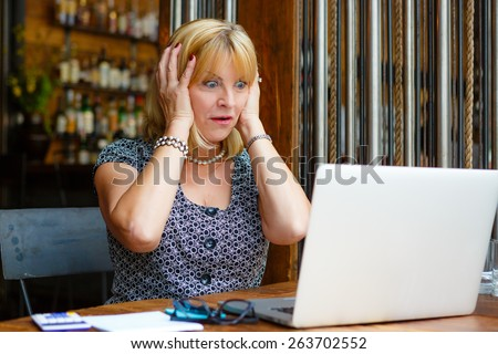 Businesswoman with laptop, Old senior woman with surprised emotion on face, looking to computer laptop sitting in summer cafe