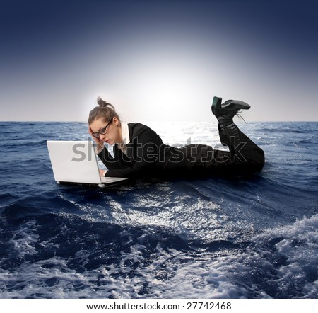businesswoman with laptop sinking in the sea - stock photo