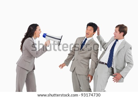 Businesswoman with megaphone yelling at colleagues against a white background - stock photo
