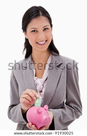 Businesswoman with money and piggy bank against a white background - stock photo
