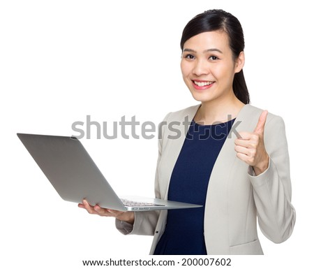 Businesswoman with notebook computer and thumb up - stock photo