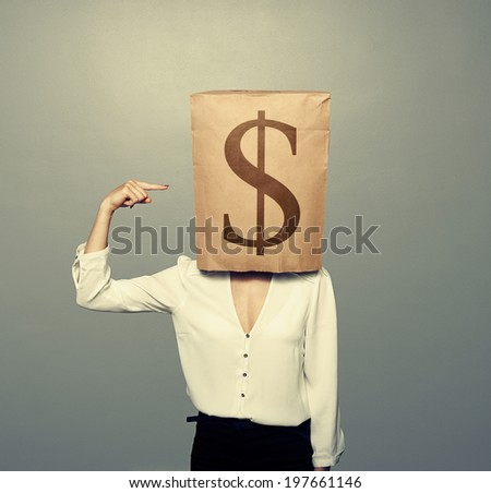 businesswoman with paper bag on her head pointing at dollar background - stock photo