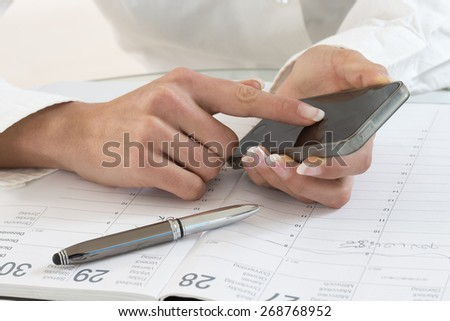 Businesswoman with phone and  calendar  - stock photo