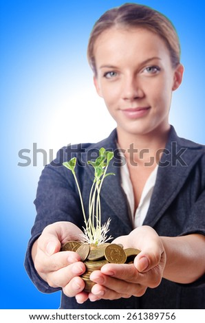 Businesswoman with seedlings and coins - stock photo