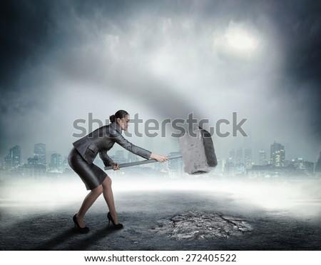 Businesswoman with sledgehammer - stock photo