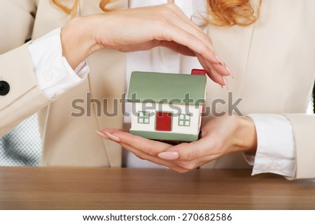 Businesswoman with small house by a desk. - stock photo