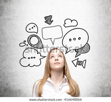 Businesswoman with speech and thought bubbles on concrete wall - stock photo