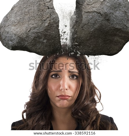 Businesswoman with split boulder above her head - stock photo
