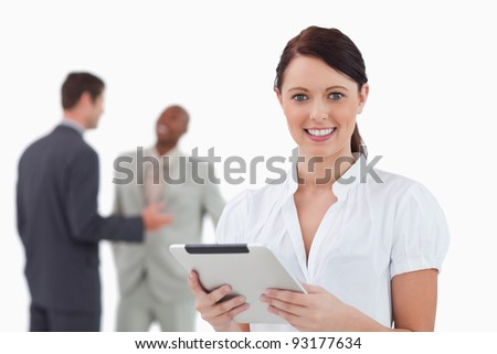 Businesswoman with tablet and colleagues behind her against a white background - stock photo