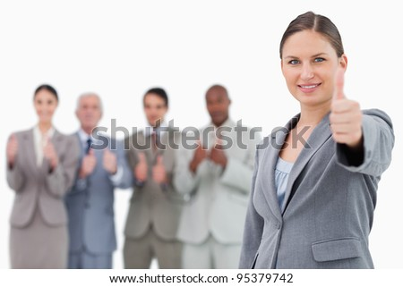 Businesswoman with thumb up and colleagues behind her against a white background