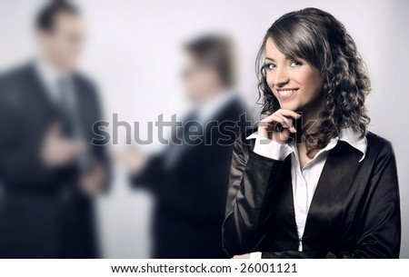 Businesswoman with two businessman in the background - stock photo