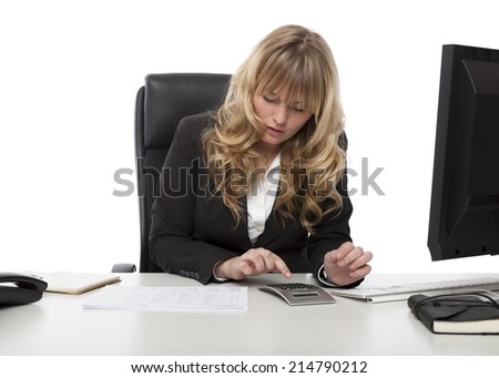 Businesswoman working at her desk doing calculations for a report that she is analyzing
