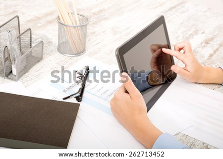 Businesswoman working at the office with the tablet and some documents