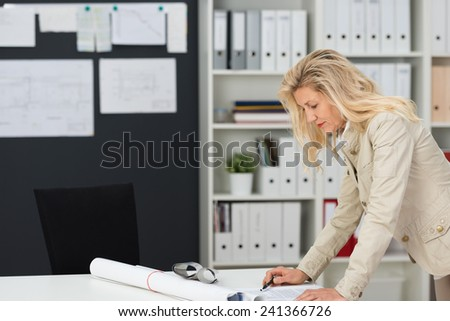 Businesswoman working in her office standing at her desk reading a document with a rolled up poster or architectural drawing alongside her, shelving background with office binders - stock photo