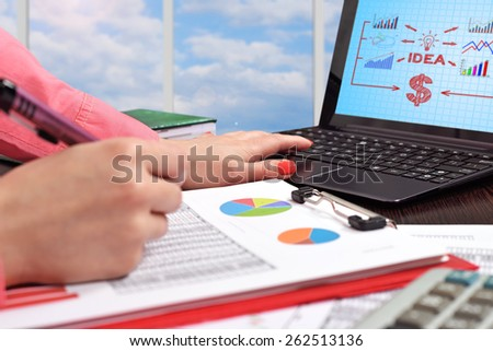 businesswoman working in office with laptop - stock photo