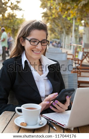 Businesswoman working in the outdoor cafe - stock photo