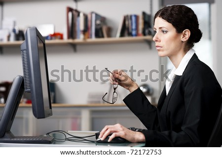 businesswoman working on a computer in an office. - stock photo