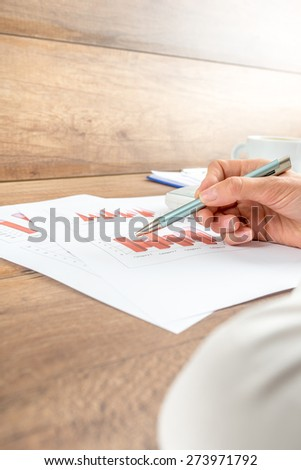 Businesswoman working on a report analysing statistical graphs, low angle of her hand and paperwork. - stock photo