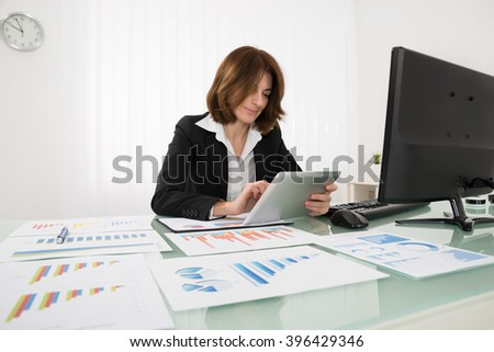 Businesswoman Working On Digital Tablet With Graphs On Desk
