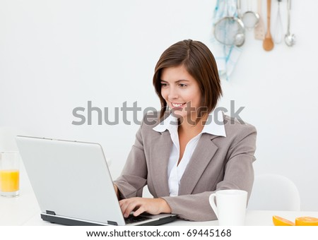 Businesswoman working on her laptop at home - stock photo