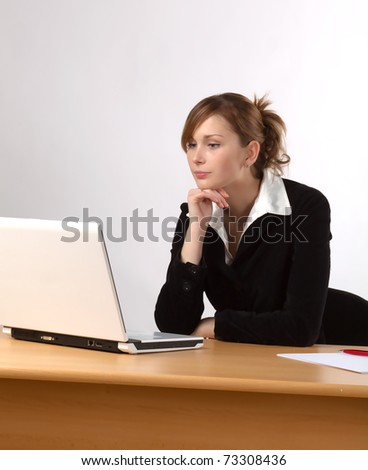 Businesswoman working on laptop at a desk, isolated