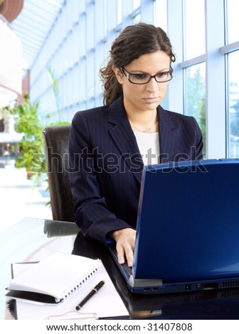 Businesswoman working on laptop computer at office lobby. - stock photo