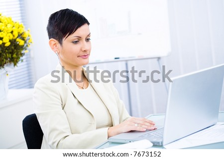 Businesswoman working on laptop computer in brightly lit office, smiling.