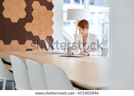 Businesswoman working on paperwork in modern office boardroom - stock photo