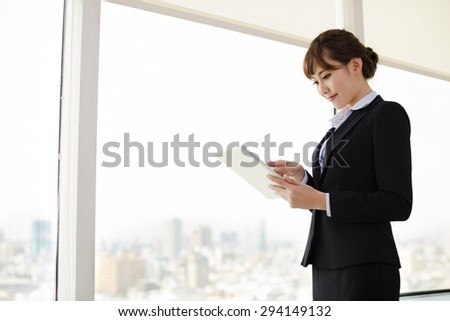 Businesswoman Working On Tablet Computer in Office - stock photo