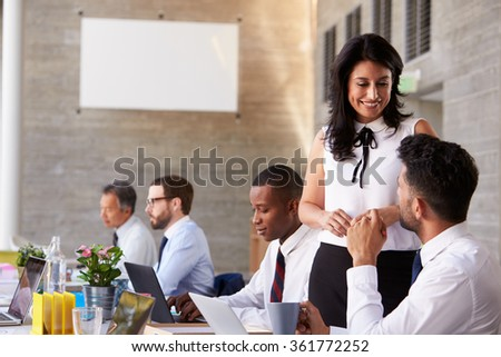 Businesswoman Working With Colleagues At Boardroom Table - stock photo