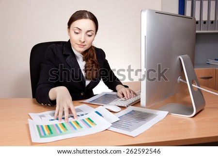 Businesswoman working with financial report at office - stock photo