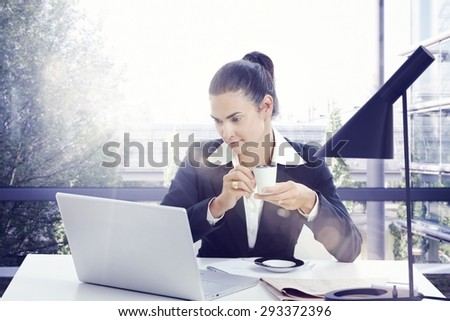 Businesswoman working with laptop in sunny office drinking morning coffee. - stock photo