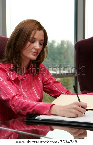 Businesswoman working writing a proposal in a meeting room - stock photo