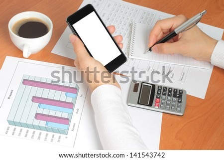 Businesswoman works at her workplace with smartphone, graphs and tables - stock photo