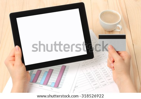 Businesswoman works at her workplace with Tablet PC and credit card - stock photo