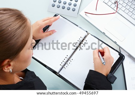 Businesswoman writing into notebook, overhead shot. - stock photo