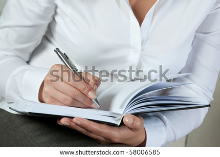 businesswoman writing on notepad - stock photo