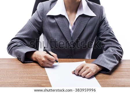 Businesswoman writing on paper at the desk.